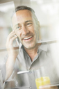 Older man talking on cell phone at breakfast - CAIF14847