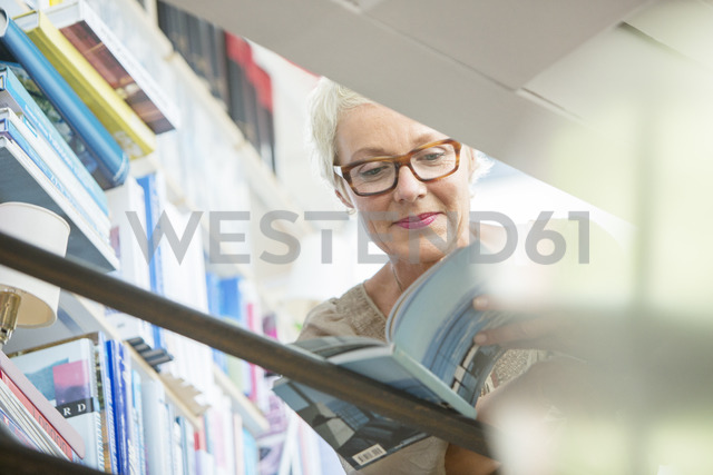 Low angle view of older woman reading book - CAIF14850