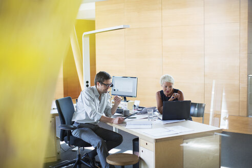 Business people talking at office desk - CAIF14886