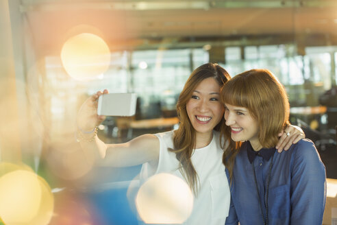 Businesswomen taking cell phone selfie in office - CAIF14940