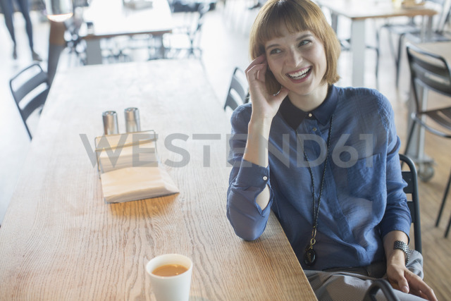 Businesswoman laughing at cafeteria table - CAIF14949