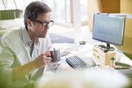 Businessman drinking cup of coffee at office desk - CAIF14952