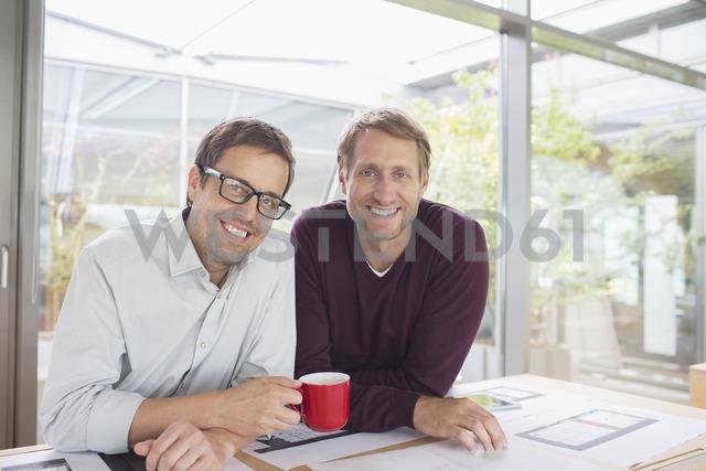 Businessmen smiling at office desk - CAIF14967