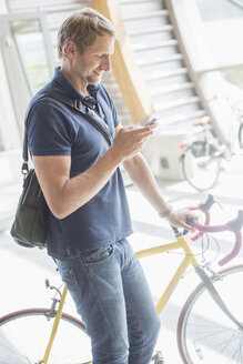 Man using cell phone and holding bicycle - CAIF14973