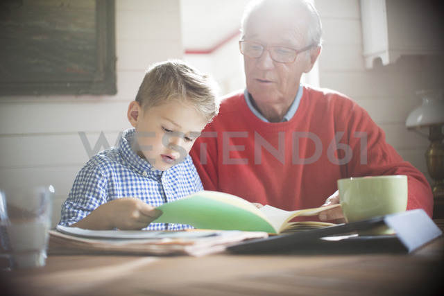Boy reading with grandfather at table - CAIF14979