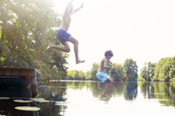 Father and son jumping into lake - CAIF14985