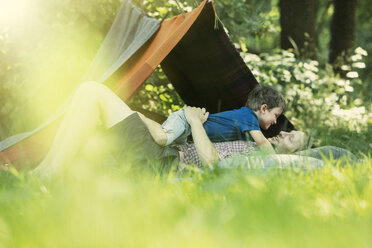 Father and son laying in grass near camping tent - CAIF14988
