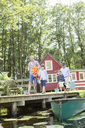 Brothers, father and grandfather walking on dock - CAIF14997