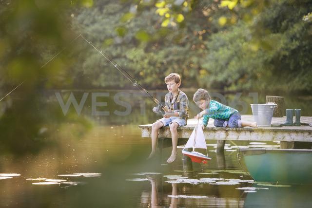 Boys fishing and playing with toy sailboat at lake - CAIF15003