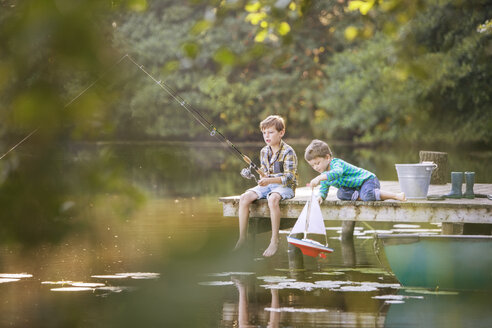 Boys fishing and playing with toy sailboat at lake - CAIF15003