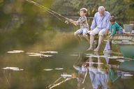 Grandfather and grandsons fishing and playing with toy sailboat at lake - CAIF15006