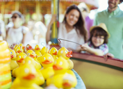 Boy trying to catch rubber duck on fishing game in amusement park - CAIF15024