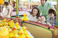 Parents with two children having fun with fishing game in amusement park - CAIF15030