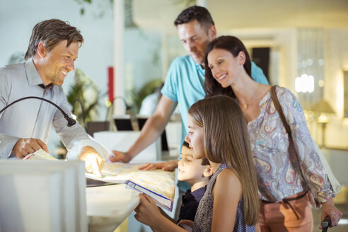 Family with two children at reception desk in hotel lobby - CAIF15054
