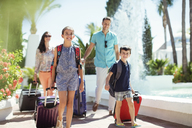 Family with suitcases passing by fountain in tourist resort - CAIF15060