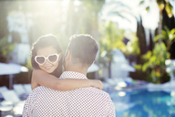 Father carrying daughter wearing heart shaped sunglasses by swimming pool - CAIF15063