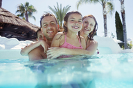 Portrait of happy family with son and daughter in swimming pool - CAIF15066