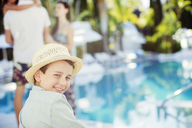 Portrait of smiling boy wearing sun hat sitting by swimming pool - CAIF15072