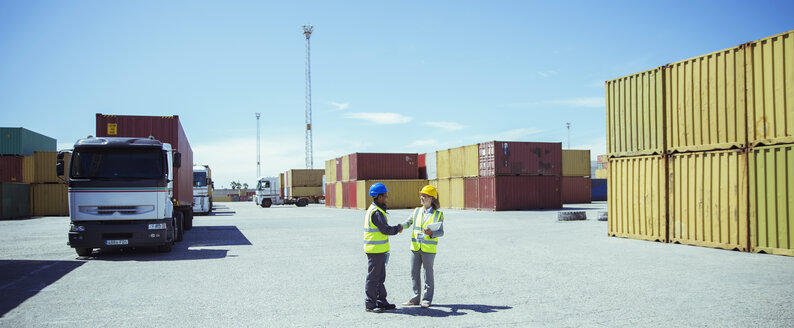 Workers talking near cargo containers - CAIF15090