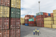 Businessmen and worker walking near cargo containers - CAIF15102