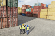 Businessmen and worker talking near cargo containers - CAIF15105