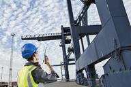 Worker using walkie-talkie under cargo crane - CAIF15111