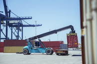Crane lifting cargo container onto truck - CAIF15123