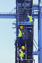 Businessman and workers climbing stairs on cargo crane - CAIF15129