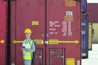 Businesswoman smiling near cargo containers - CAIF15132