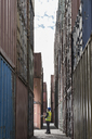 Worker standing between cargo containers - CAIF15141