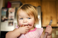 Girl looking away while eating chocolate at home - CAVF06067