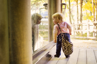 Baby girl with purse looking through window - CAVF06070