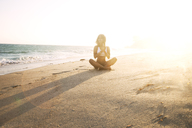 Woman meditating while sitting on sand at beach - CAVF06085