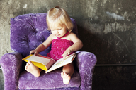 Baby girl looking picture book while sitting on arm chair at home - CAVF06088