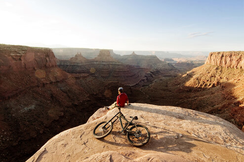 High angle view of mountain biker with bicycle sitting on cliff against sky - CAVF06187