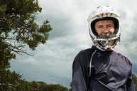 Portrait of man wearing crash helmet against cloudy sky - CAVF06193