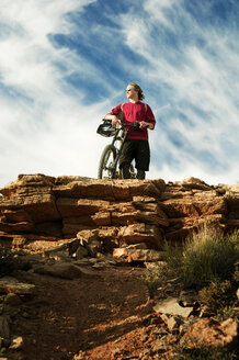 Low angle view of man with bicycle looking away while standing on cliff against sky - CAVF06196