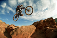 Low angle view of mountain biker performing stunt while cycling - CAVF06199