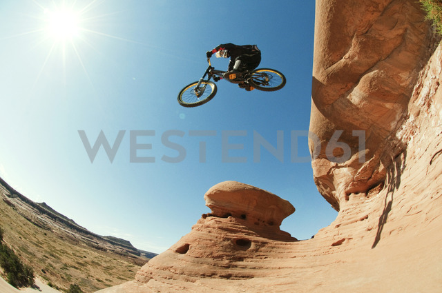Low angle view of mountain biker jumping from cliff against clear blue sky - CAVF06208 - Cavan Images/Westend61