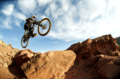 Cyclist jumping from rocks against cloudy sky - CAVF06217