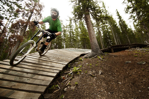 Mountain biker cycling on sports ramp in forest - CAVF06226