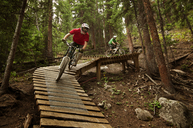 Cyclists cycling on sports ramp amidst trees in forest - CAVF06229