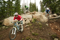 Mountain bikers cycling on rocks in forest - CAVF06235