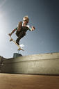 Low angle view of man jumping with skateboard against sky - CAVF06244