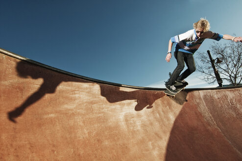 Low angle view of man skateboarding on sports ramp against sky - CAVF06262