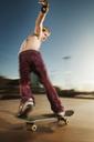 Shirtless man skateboarding on sports ramp against sky - CAVF06265