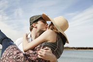Man kissing girlfriend while carrying at beach - CAVF06307