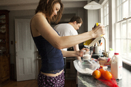 Couple preparing breakfast while standing at home - CAVF06322