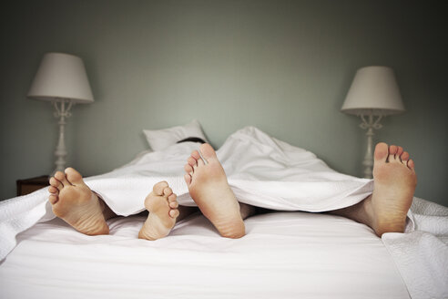 Couple lying on bed at home - CAVF06331