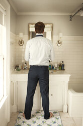 Rear view of man getting dressed while standing at mirror in home - CAVF06334